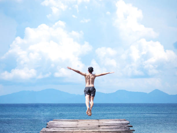 homme asiatique, sautant de pont en bois en mer d'un bleu - plonger dans photos et images de collection