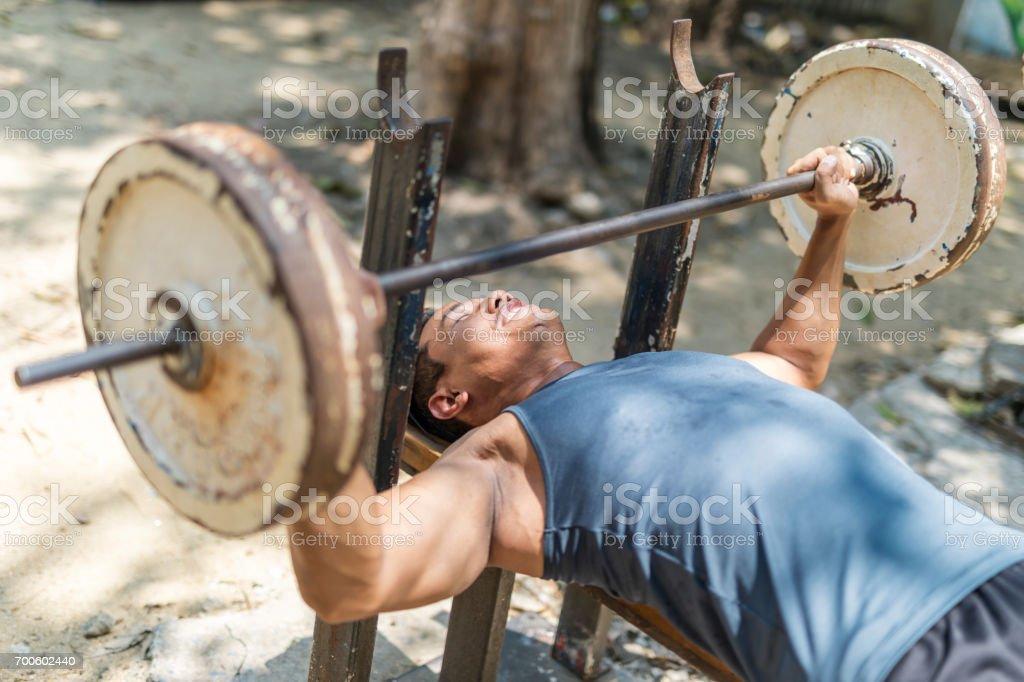 Asian Man Lifting Weights at a Makeshift Outdoor Gym stock photo