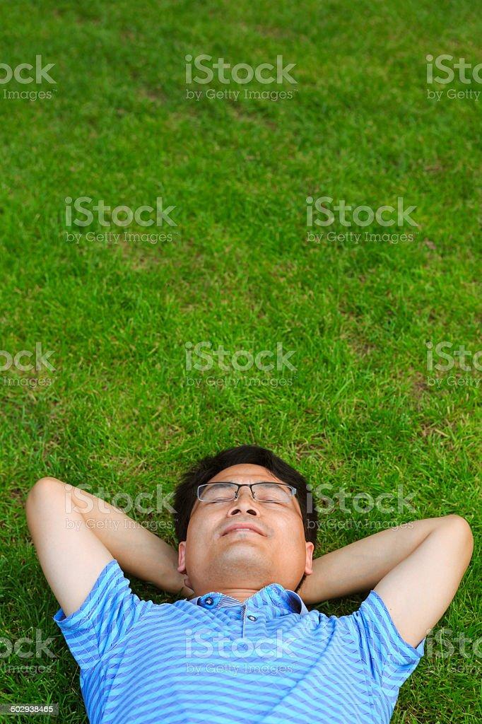 Asian man lying on the grassland royalty-free stock photo