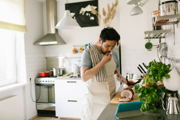 Asian man making chashu pork with the help of digital cookbook stock photo