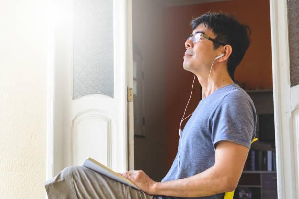 Asian man meditating and writing gratitude journal stock photo