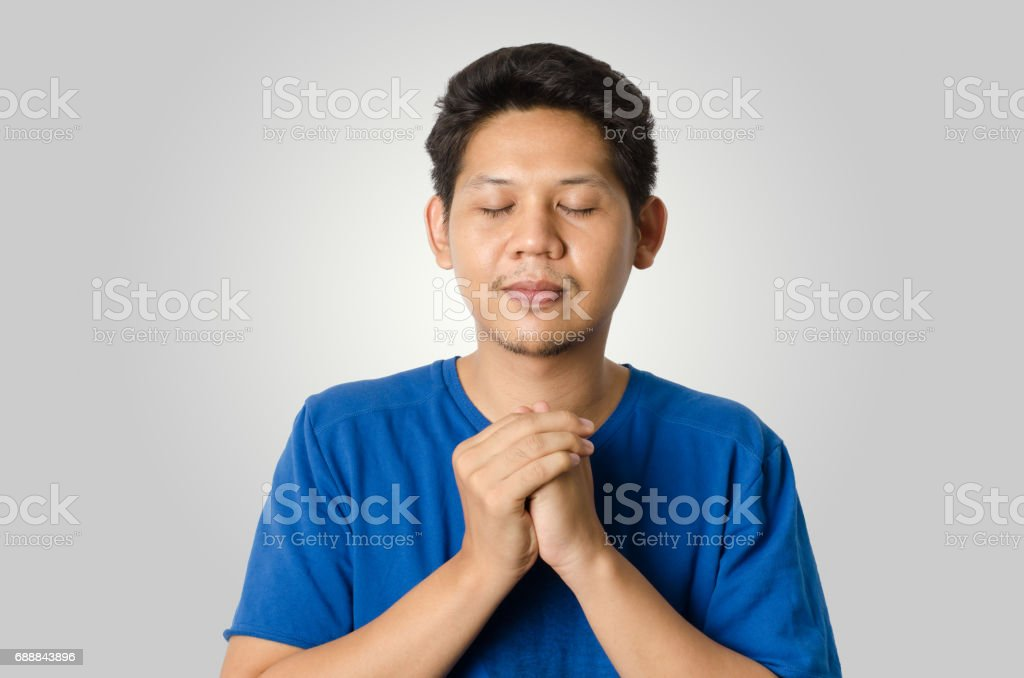Asian man meditating isolated on gray background stock photo