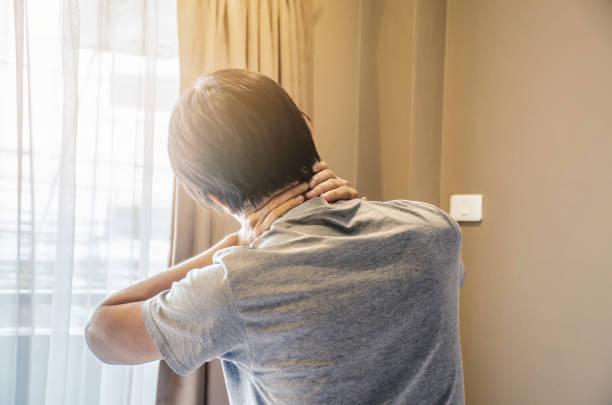 asiatischer mann nackenschmerzen nach dem aufwachen morgens im bett im schlafzimmer - schultersteife stock-fotos und bilder