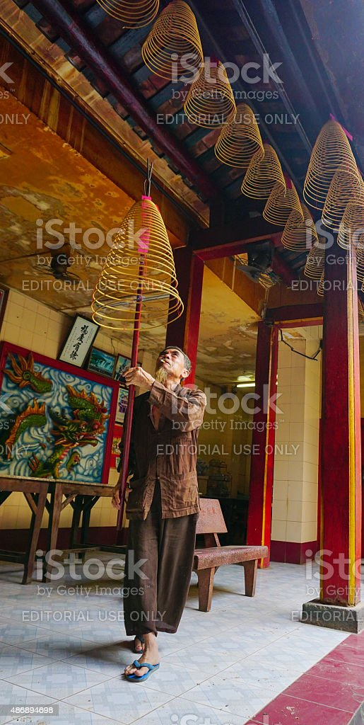 Asian man offering incense sticks for the Gods stock photo