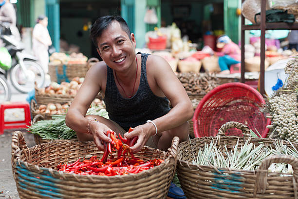 Asian Man on Street Market Smile Sell Red Chilly Pepper stock photo