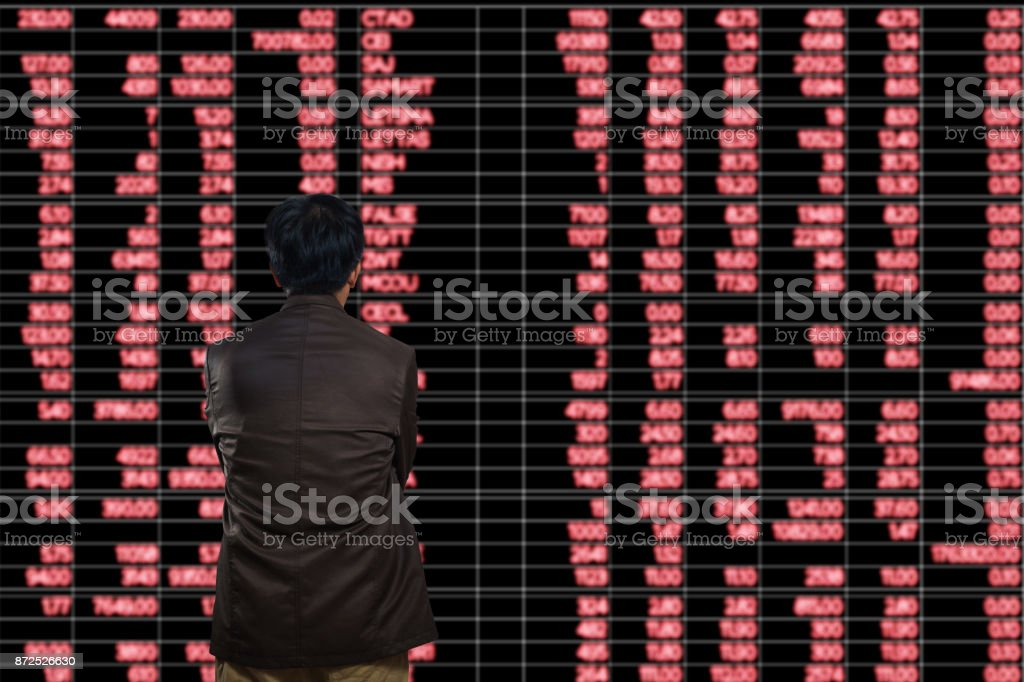 Asian Man or Male Looking at Stock Trading data on Display Board at Stock Exchange Market as Business financial investment concept. stock photo
