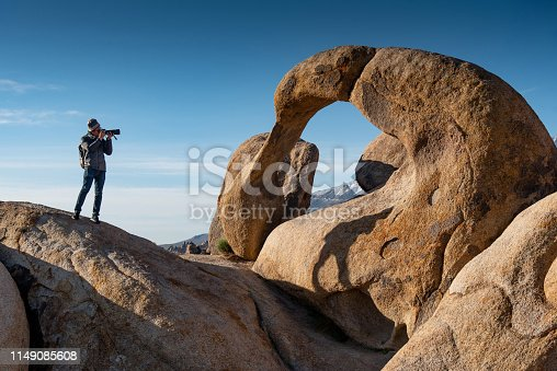 Asian man photographer and traveler holding camera taking photo through the mobius arch stone at Alabama Hills, Lone pine, USA. Travel photography concept