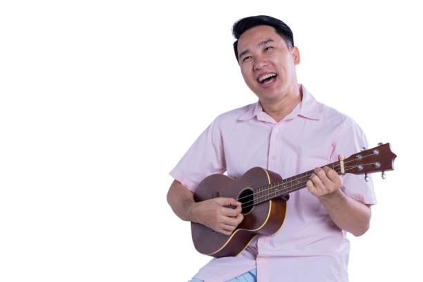asiatischer mann ukulele spielen mit glück auf weißem hintergrund - ukulele songs stock-fotos und bilder