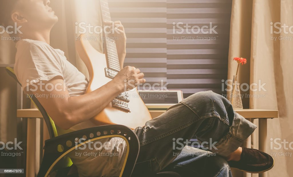 asian man playing electric guitar for relaxation in the room stock photo