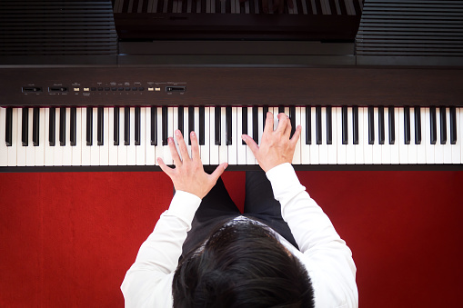 Asian man playing piano. Top view with red floor background. Favorite music instrument for learning basic of rhythm and music skill.
