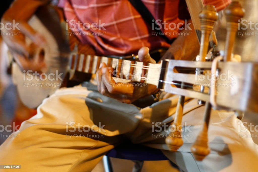 Asian man playing stringed instrument, busking at a local market, Northern Thailand, Southeast Asia stock photo