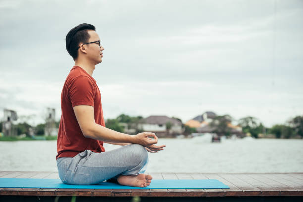 asian man playing with a yoga school at yoga class in early morning. lifestyle and healty concept. - poprawna postawa zdjęcia i obrazy z banku zdjęć