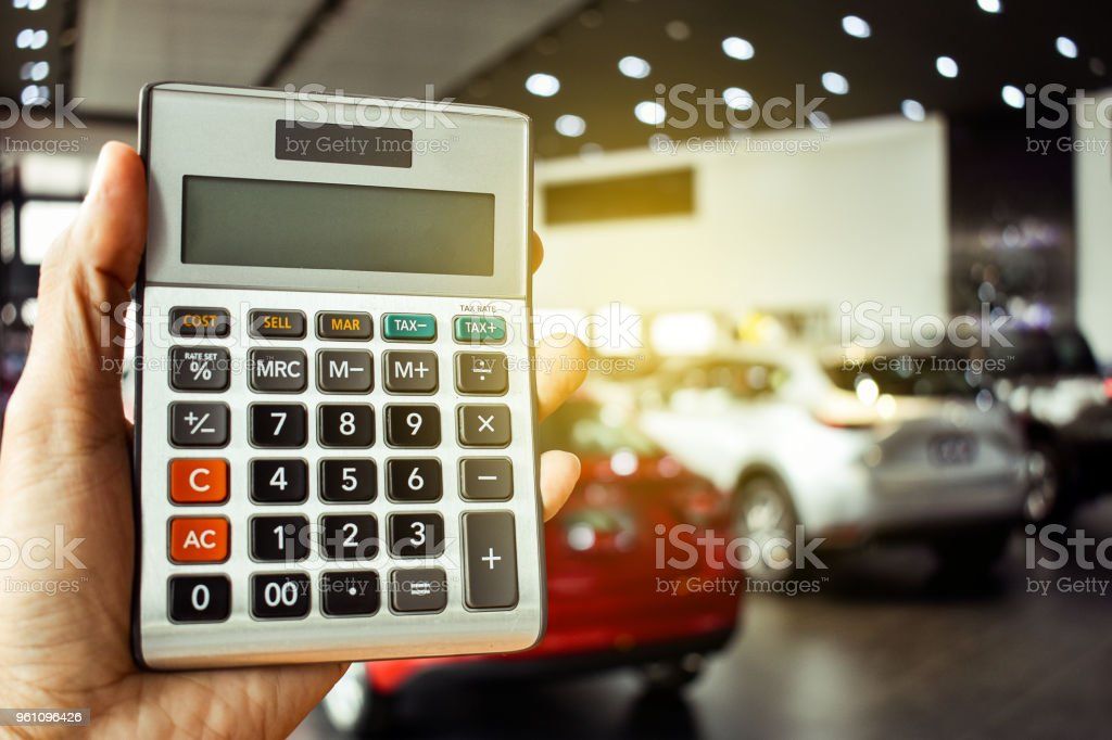 Asian Man Pressing Calculator For Business Finance On Car Showroom