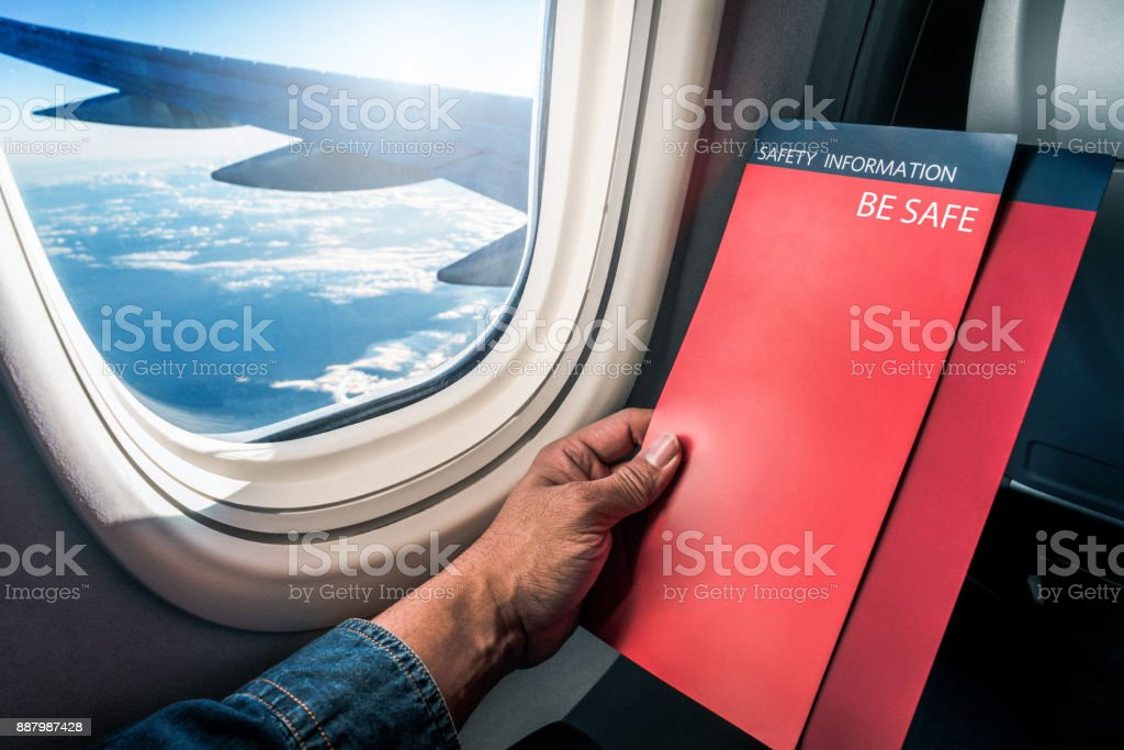 Asian man read flight safety instructions on card board flight. stock photo