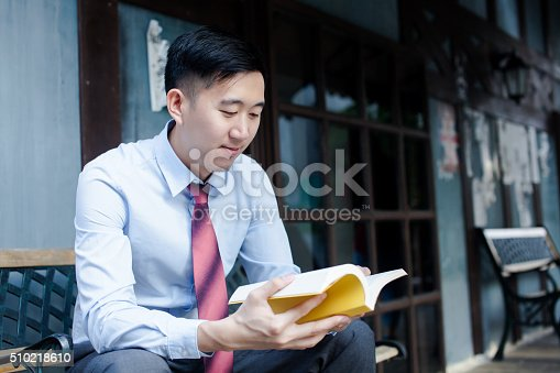 istock Asian Man Reading a Book Sitting on Bench 510218610