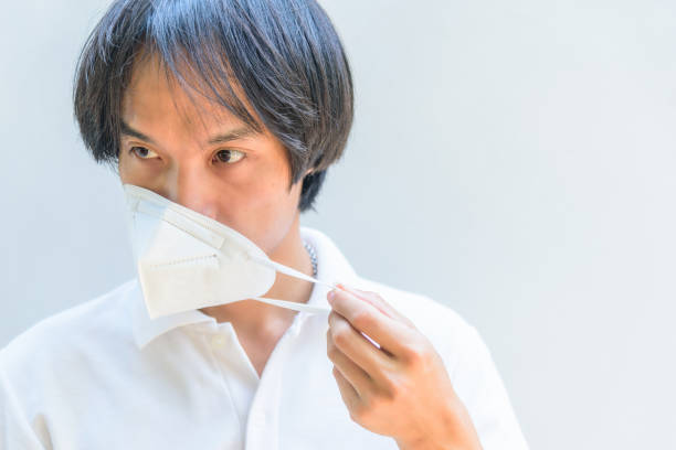 A asian man remove the N95 mask from his face stock photo