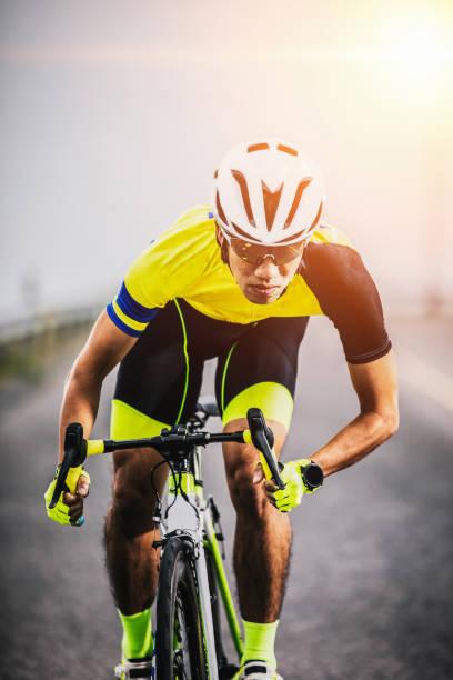 hombre asiático montando en bicicleta en carretera de asfalto contra el amanecer - foto de stock