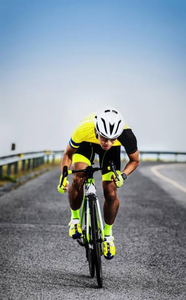hombre asiático montando en bicicleta en carretera de asfalto - foto de stock
