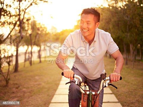 istock asian man riding bike outdoors at sunset 482393278