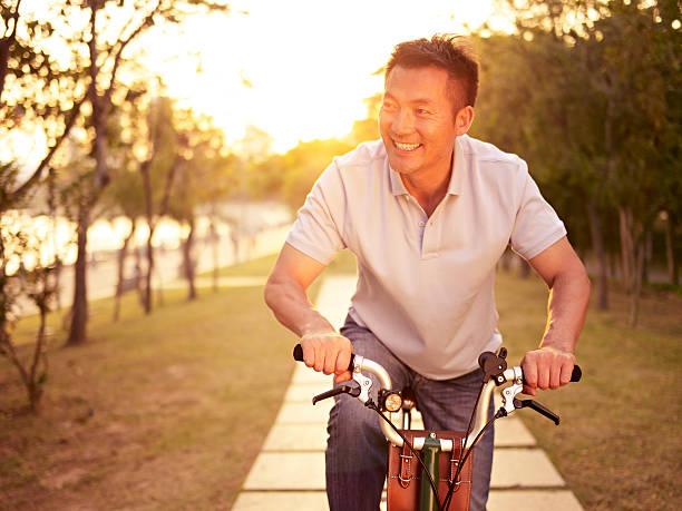 asian man riding bike outdoors at sunset stock photo