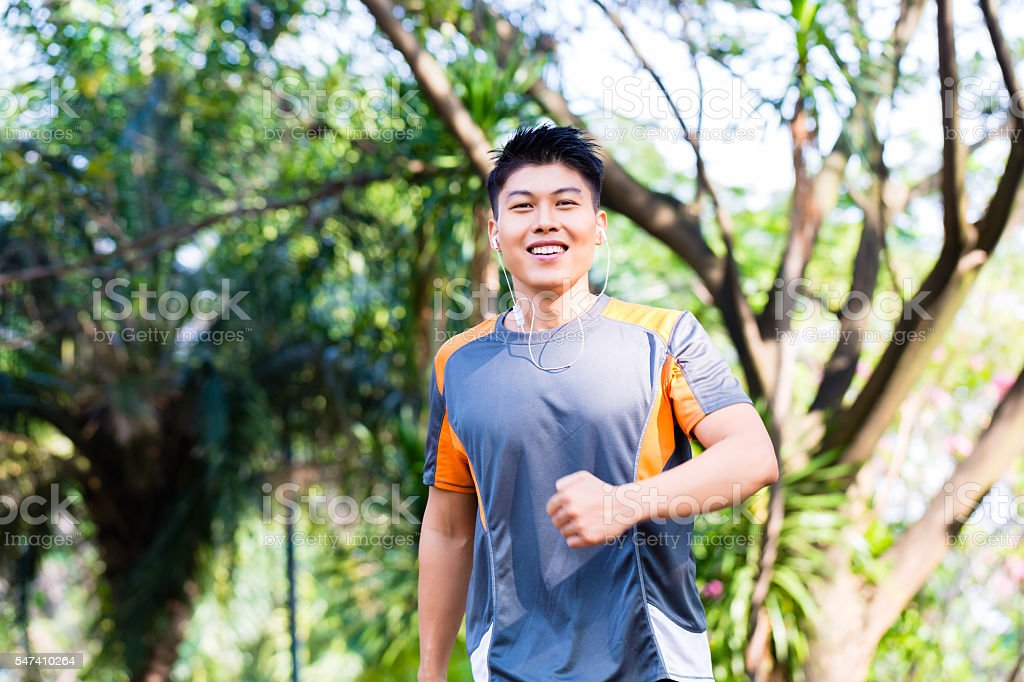 Asian man running in city park stock photo