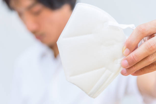 A asian man show N95 mask for protect PM2.5 Dust and disease stock photo