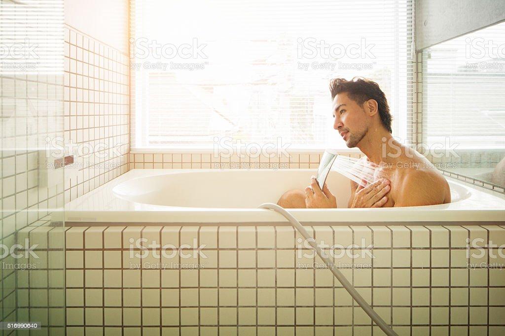 Asian man showering in Japanese bathtub stock photo