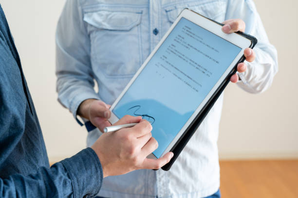 asiatischer mann unterzeichnet digitalen vertrag auf tablet, nahaufnahme - unterschrift stock-fotos und bilder