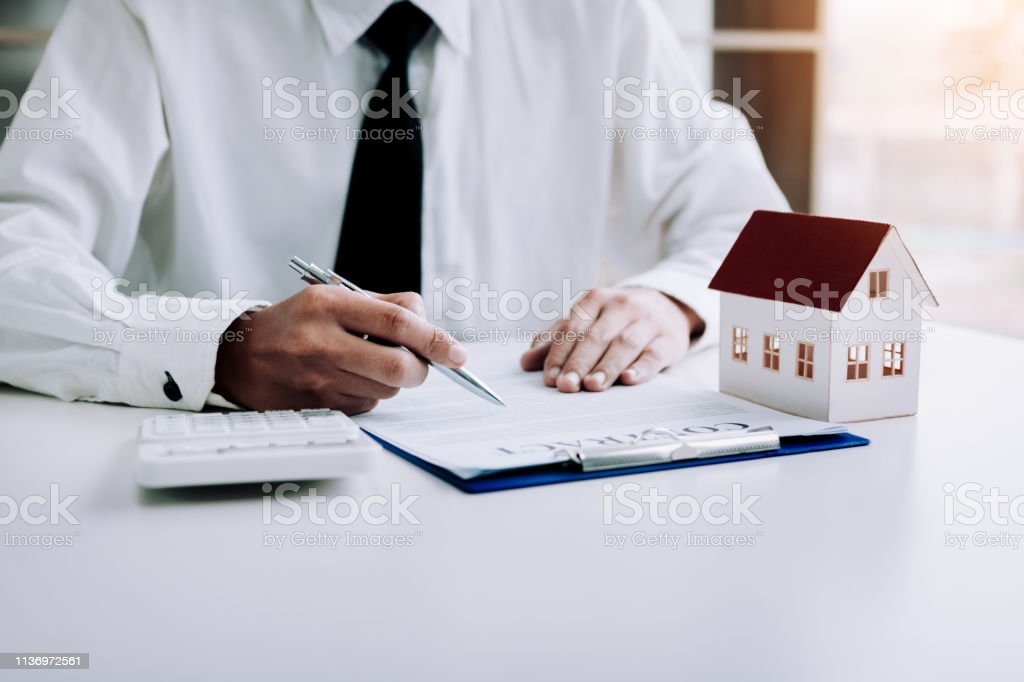 Asian man signing paper contract agreement for house with model home.