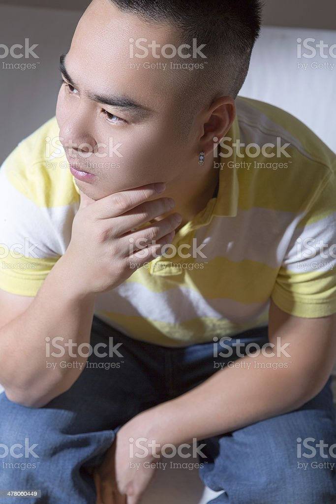 Asian man sitting on couch royalty-free stock photo