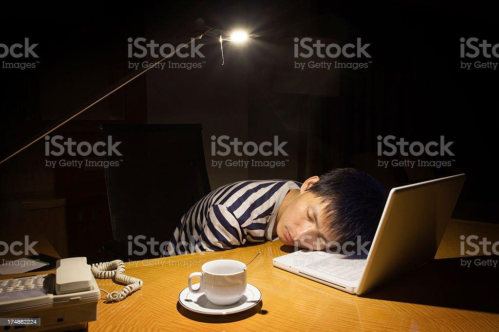 asian man sleeping on laptop royalty-free stock photo