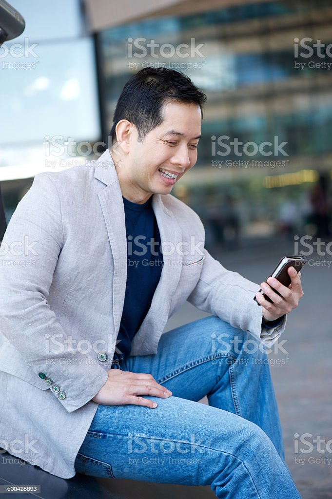 Asian man smiling with cellphone royalty-free stock photo