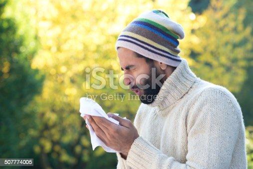 istock Asian Man Sneezing into Tissue 507774005
