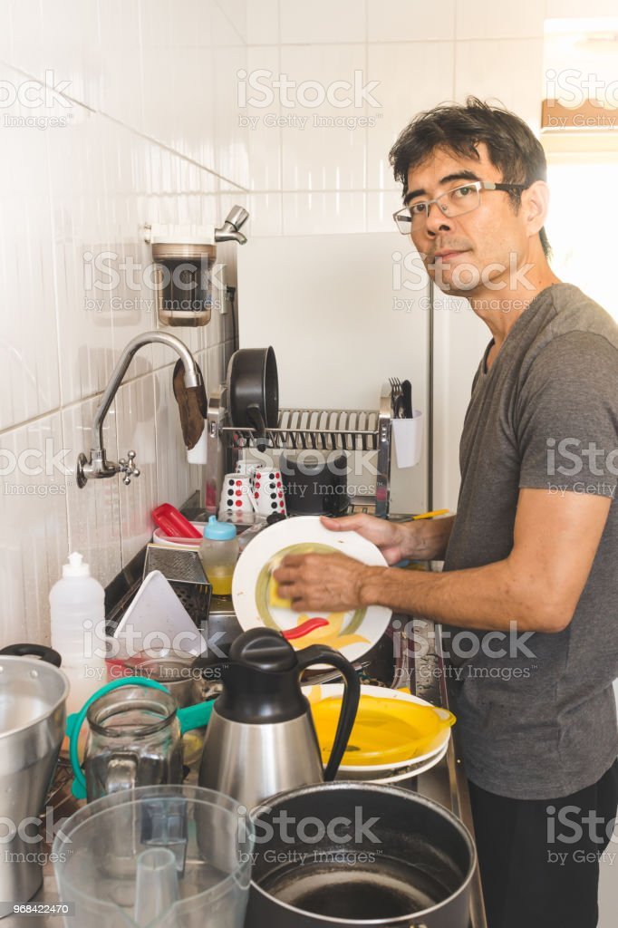 Asian man standing and washing dishes on a messy kitchen. Candid...