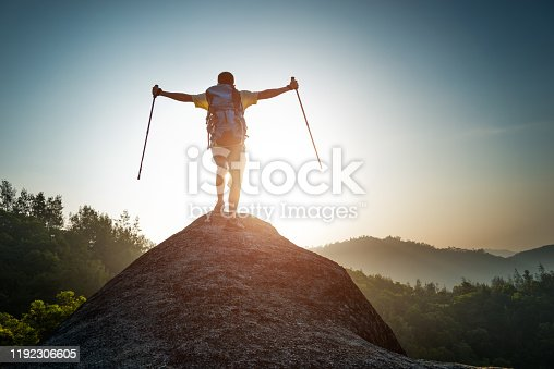 Asian man standing at mountain peak with arms and hands raised in air.