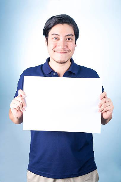 Asian man standing with empty horizontal blank paper in hands stok fotoğrafı