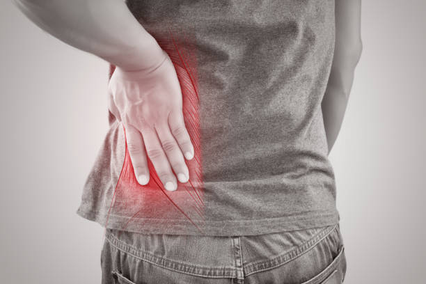 Asian man suffering from muscle waist pain injury, People with back pain symptoms against gray background stock photo