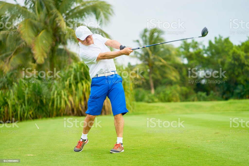 Asian man swinging club in golf course in summer stock photo