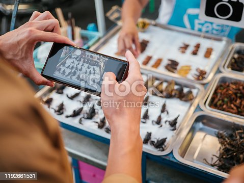 Tourist asian man taking picture of food with smartphone, a set of delicious traditional Thai dishes on the plate.