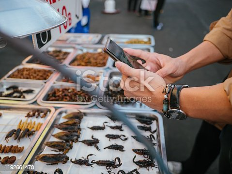 Tourist asian couple taking picture of food with smartphone at flea market in Bangkok, Thailand. Khao San Road.