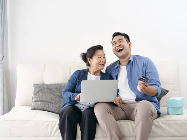 Asian man teaching his mother for shopping online, modern lifestyle concept. Asian man teaching his mother for shopping online, modern lifestyle concept. old mother son asian stock pictures, royalty-free photos & images