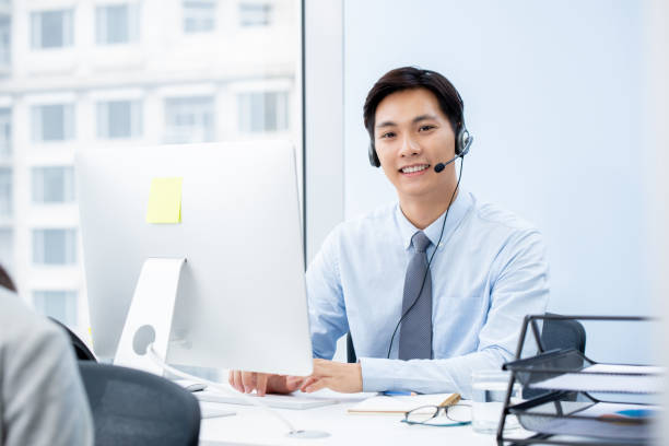 Asian man telemarketer working in offfice stock photo