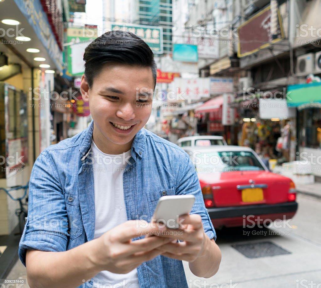 Asian man text messaging in Hong Kong foto de stock libre de derechos