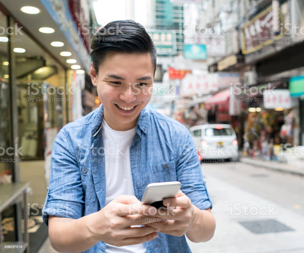 Asian man text messaging on his phone royalty-free stock photo