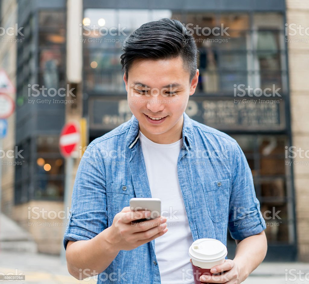 Asian man texting and having a cup of coffee royalty-free stock photo