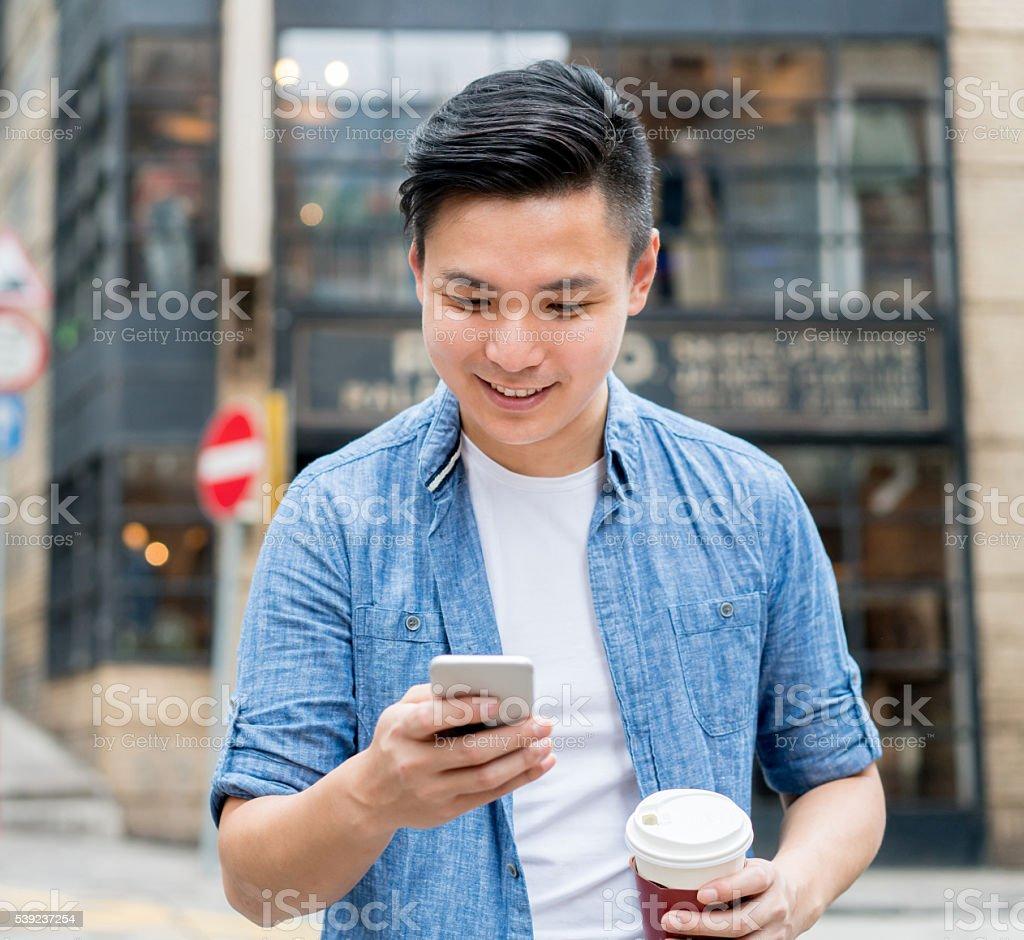 Asian man texting and having a cup of coffee foto de stock libre de derechos