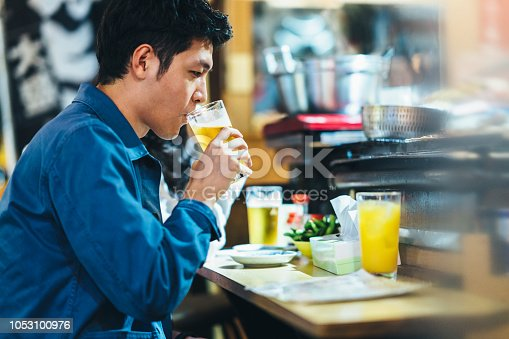 An asian man tourist is drinking beer in a street food counter at night.