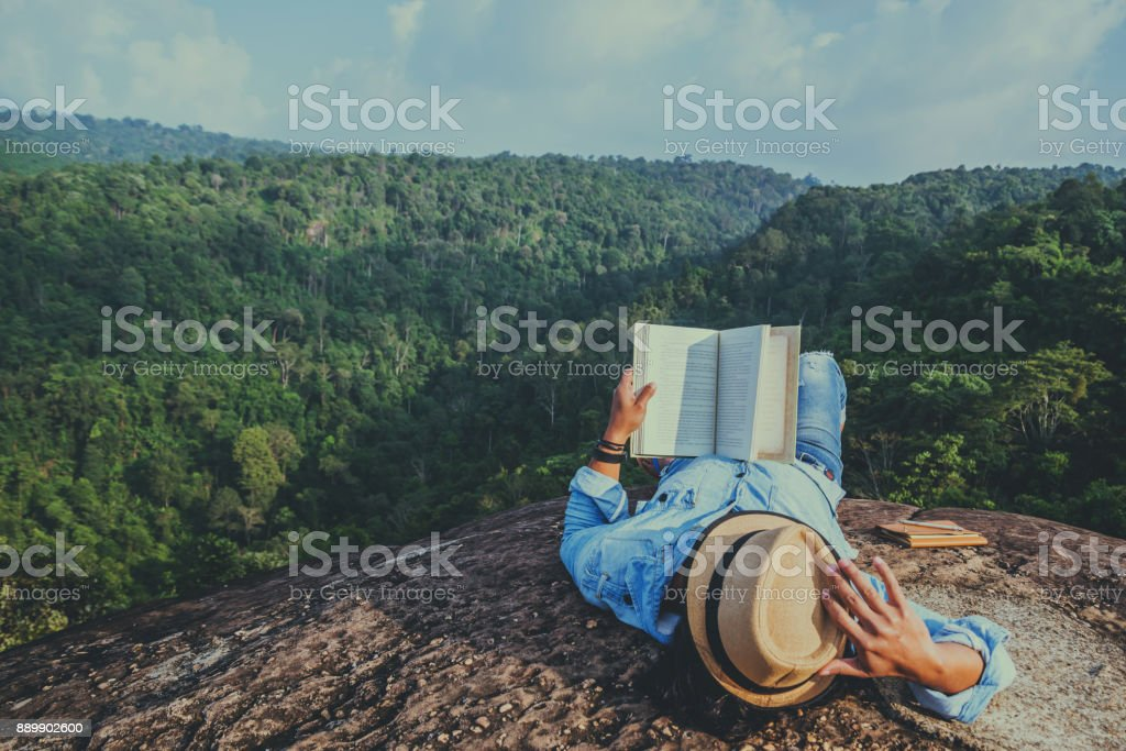 Asian man travel relax in the holiday. sleep relax read books on rocky cliffs. On the Moutain. In Thailand stock photo