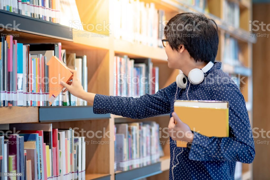 Asiatischer Studentenstufer, der Bücher aus dem Bücherregal in der College-Bibliothek für Bildungsforschung auswählt und auswählt. Bestseller-Kollektion in Buchhandlung. Stipendium oder pädagogische Opportunity – Foto