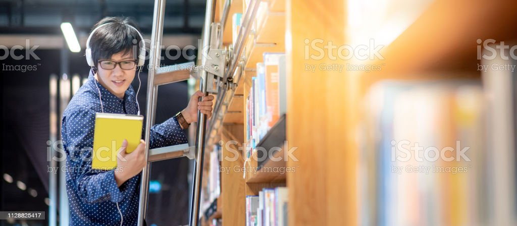 Asiatischer Student aus dem Buch, der sich aus dem Bücherregal entscheidet, während er in der Bibliothek für Bildungsforschung auf der Leiter steht. Bestseller-Kollektion in Buchhandlung. Stipendium oder Bildungschance – Foto